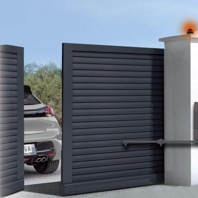 Une voiture sort d'une maison avec portail battant motorisé