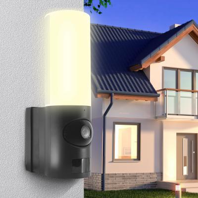 Lampe extérieure allumée sur le mure d'une maison avec une caméra de surveillance