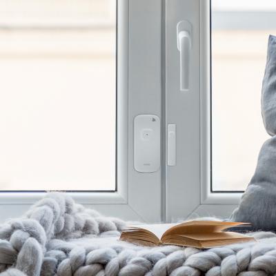 Détecteur d'ouverture posé sur une fenêtre blanche