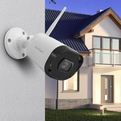 Caméra extérieure wifi fixée sur un mur avec une maison derrière