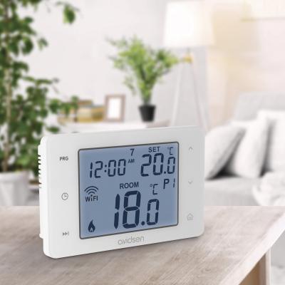 Thermostat connecté pour chaudière posé sur une table en bois