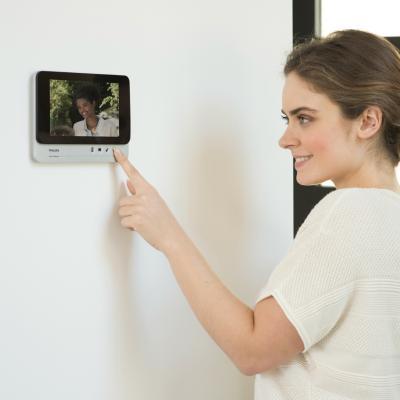 Une femme utilise l'écran du visiophone Philips Add Comfort qui est fixé sur un mur