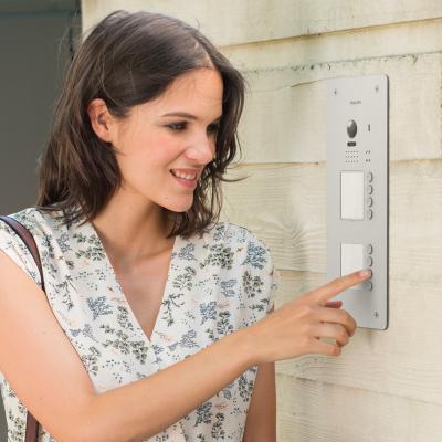 Une femme utilise la platine de rue de l'interphone Philips Hive Pro 8 appartements