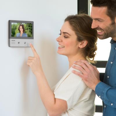 Un couple accueil une copine à travers l'écran du visiophone WelcomeHive Pro