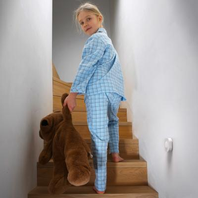 Un enfant monte dans l'escalier avec son doudou devant un détecteur de mouvement